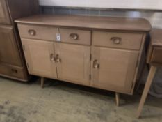 An Ercol elm sideboard (model no. 351), fitted one long drawer and one short drawer over three