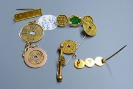 Eight assorted Chinese yellow metal amulets, four in the form of brooches, three pendants and a