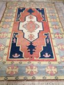 An Afghan Kazak rug, the red and blue ground field centred by an ivory cruciform medallion, woven
