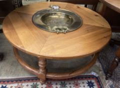 A circular pine low table inset two-handled brass brazier, diameter 108cm height 43cm