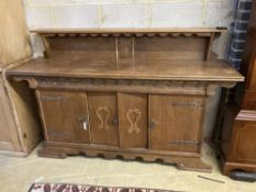 A 1930's oak Gothic inspired sideboard, width 180cm depth 50cm height 116cm