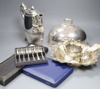 A cast white metal bowl and a collection of plated items, including a hot water pot, meat cover,