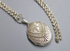 A late Victorian silver oval locket, 47mm, on a long white metal chain, 148cm, gross 124 grams.