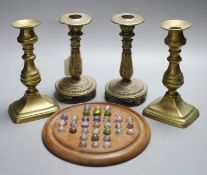 Two pairs of brass candlesticks and a solitaire board with marbles