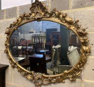 A Victorian ornate gilt oval wall mirror, width 110cm height 100cm