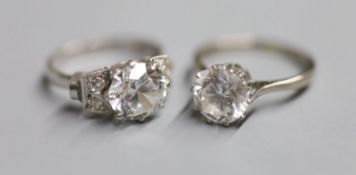 A white metal (stamped plat) single stone moissanite? and four stone diamond set dress ring, size M,