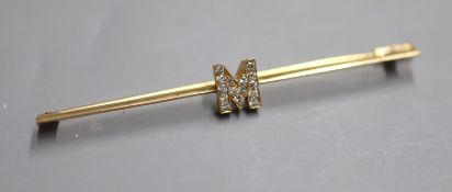 A yellow metal and diamond set initial 'M' bar brooch, 77mm, gross 4.6 grams.