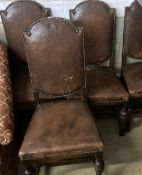 A set of four 1920's oak and tan leather dining chairs, height 109cm