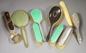 A guilloche enamel and silver-mounted three-piece brush and comb set, three other silver-mounted