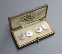 A pair of white metal mounted mother of pearl circular cufflinks, in Goldsmiths and Silversmiths