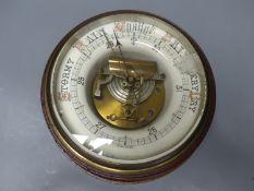 A circular wall mounted aneroid barometer, diameter 25cm