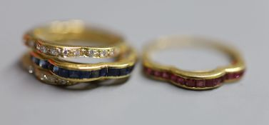 A modern continental 750 yellow metal and triple shank, sapphire, ruby and diamond set shaped half
