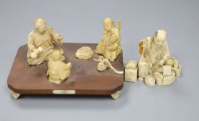 A Meiji period Japanese ivory okimono figural group, raised on a rosewood base and scrolled ivory