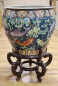 A Chinese porcelain fish bowl on stand, diameter 47cmCONDITION: Wear to the enamel colours around