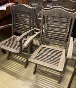 A set of six weathered teak folding garden chairs, two with arms