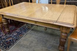 An early 20th century carved oak extending dining table, 294cm extended (three spare leaves), width