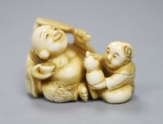 A Japanese ivory netsuke in the form of a seated Hotei and attendant, early 20th century 3cm high,