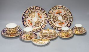 A Royal Crown Derby imari pattern 2451 cup and saucer, three cans and saucers, two bread plates, a