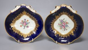 A pair of 18th century Worcester shell shaped dishes painted with flowers surrounded by rich