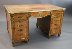 An early 20th century Louis XVI style ormolu mounted satinwood and rosewood kneehole desk, with pale