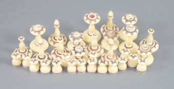 A 19th century Muslim ivory chess set, the two sides with engraved red and brown geometric motifs,