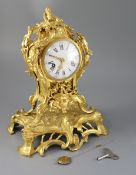 A mid 18th century French ormolu mantel clock, with ornate pierced foliate scroll case and enamelled