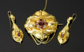 A Victorian 15ct gold, garnet and white stone set demi parure, comprising a shaped oval brooch, 46mm
