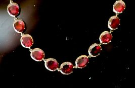 An early 19th century gold and garnet set necklace, set with thirty six oval cut garnets, 38cm,