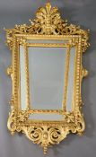 A Louis XIV style carved giltwood wall mirror, with putto mask, fruit and foliate scroll crest,