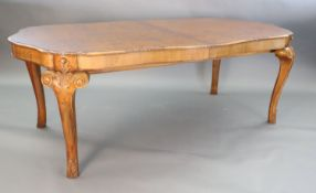 A Queen Anne style burr walnut extending dining table, the shaped top with moulded leaf carved
