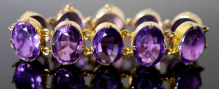 A Victorian style gold and ten stone oval cut amethyst set bracelet, 18.5cm, gross 64.9 grams.