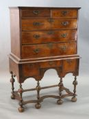 An early 18th century walnut chest on stand, with veneered top, two short and three graduated long