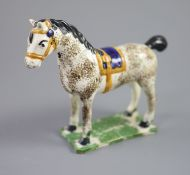 A North Country pearlware figure of a dapple horse with blue saddle, c.1800-20 on a slab base, 14.