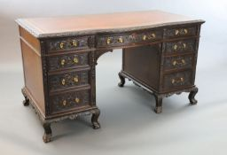 An Edwardian foliate carved mahogany serpentine kneehole desk, with gilt brown skiver, central