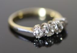 An early 20th century 18ct gold, platinum and graduated four stone diamond ring, size O, gross 3.6