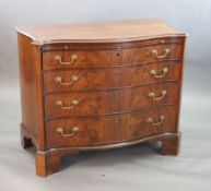 A George III mahogany and rosewood banded serpentine fronted chest, fitted brushing slide and four