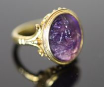 A 19th century style gold ring set with an antique intaglio oval amethyst, carved with a seated