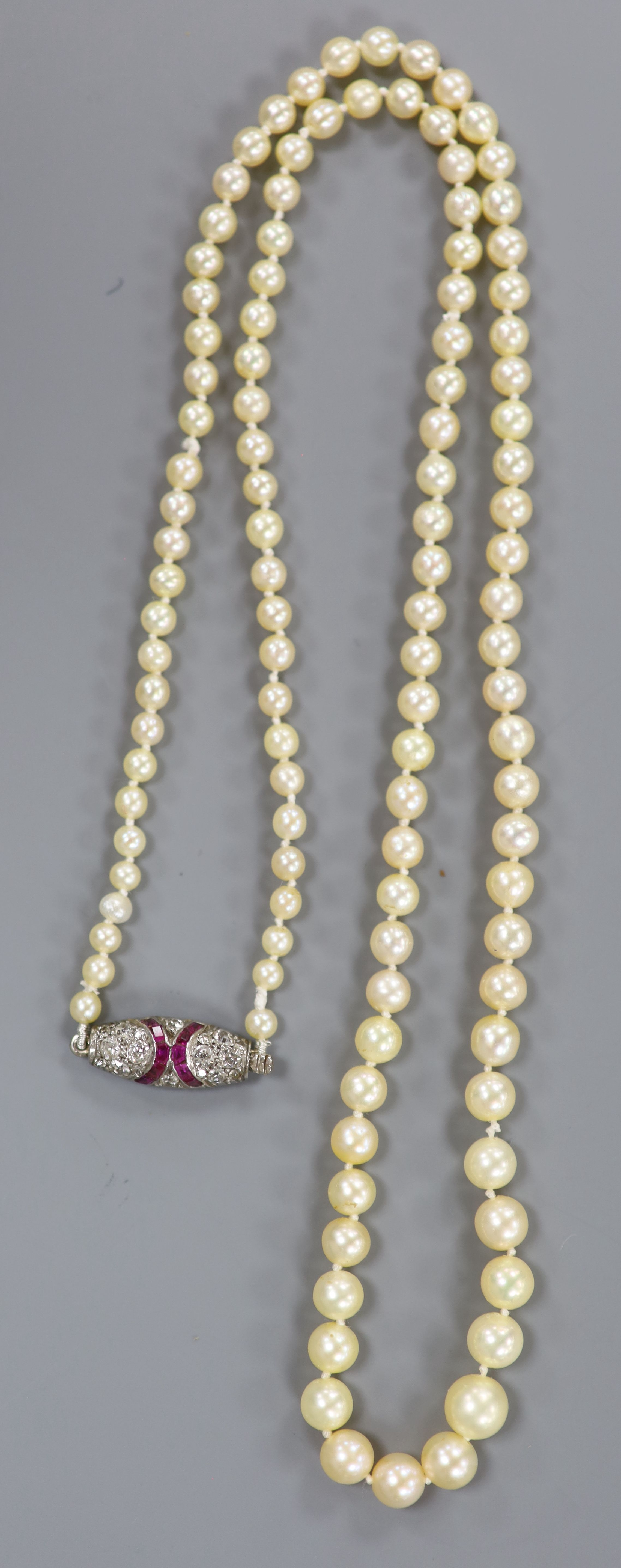An early 20th century single strand graduated seed pearl necklace, with white metal ruby and diamond - Image 2 of 3