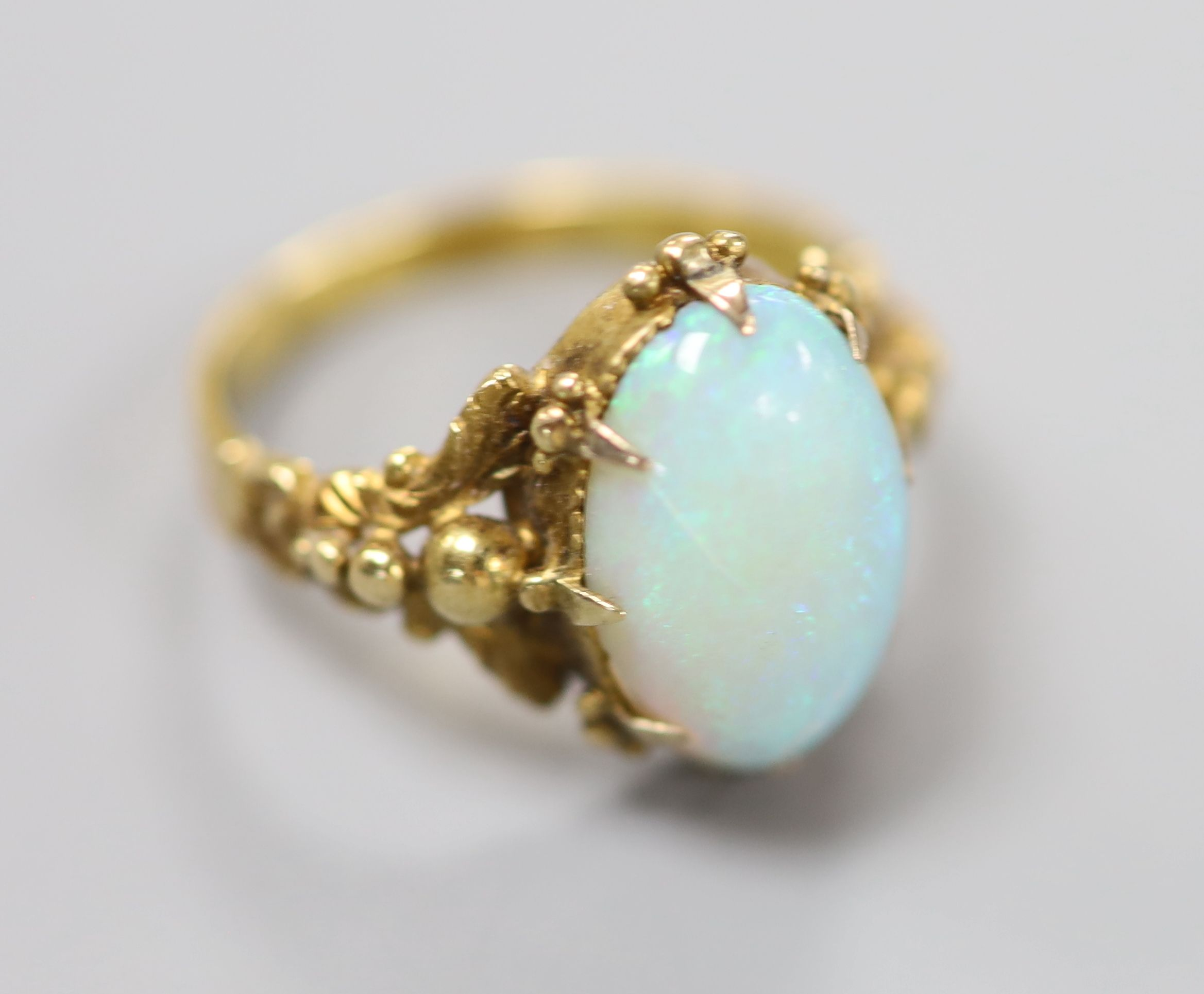 A 19th century yellow metal and oval white opal set dress ring, size M, gross 4.1 grams.CONDITION: