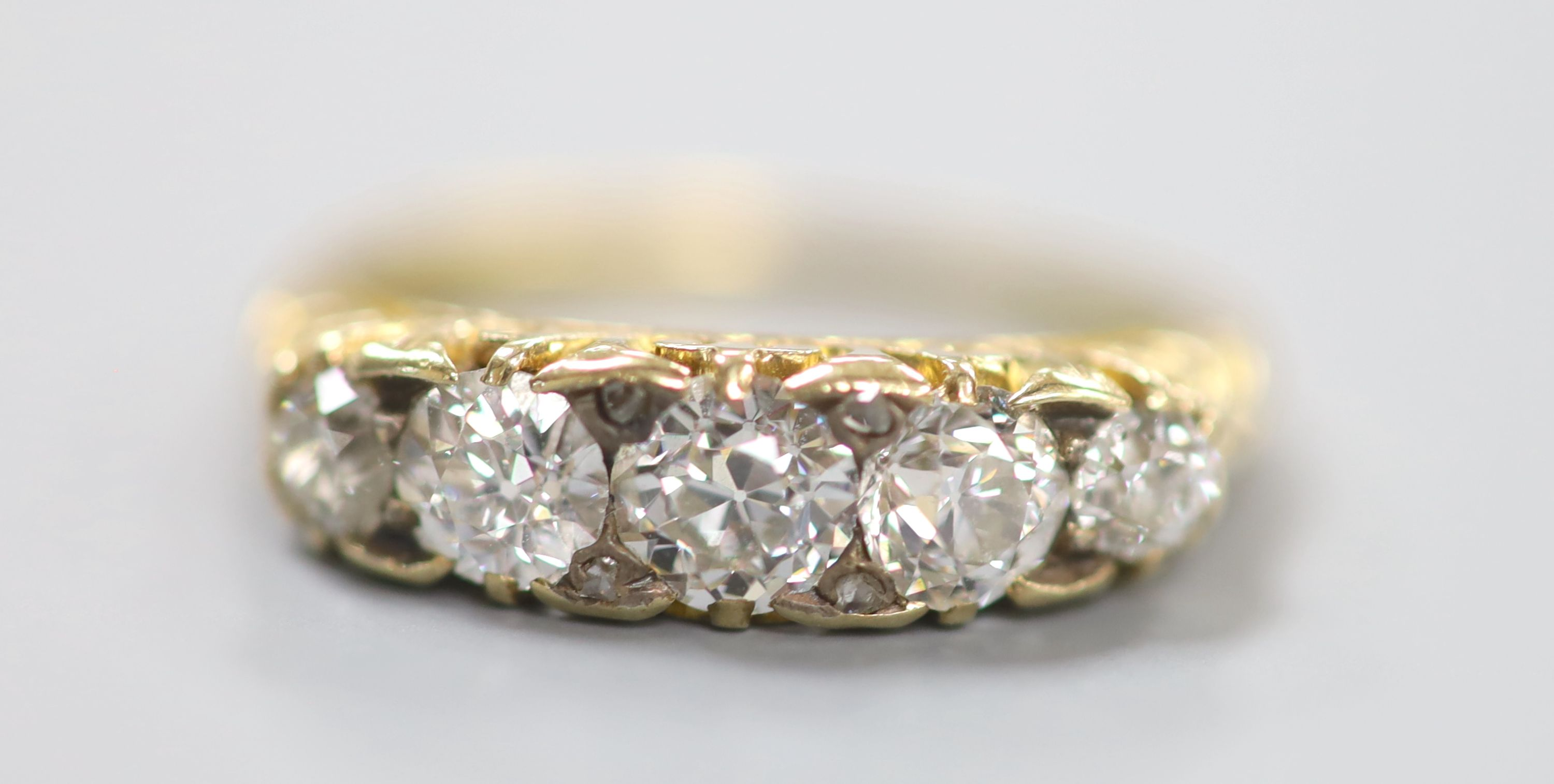 An early 20th century yellow metal and graduated five stone diamond set half hoop ring, size N, - Image 2 of 4