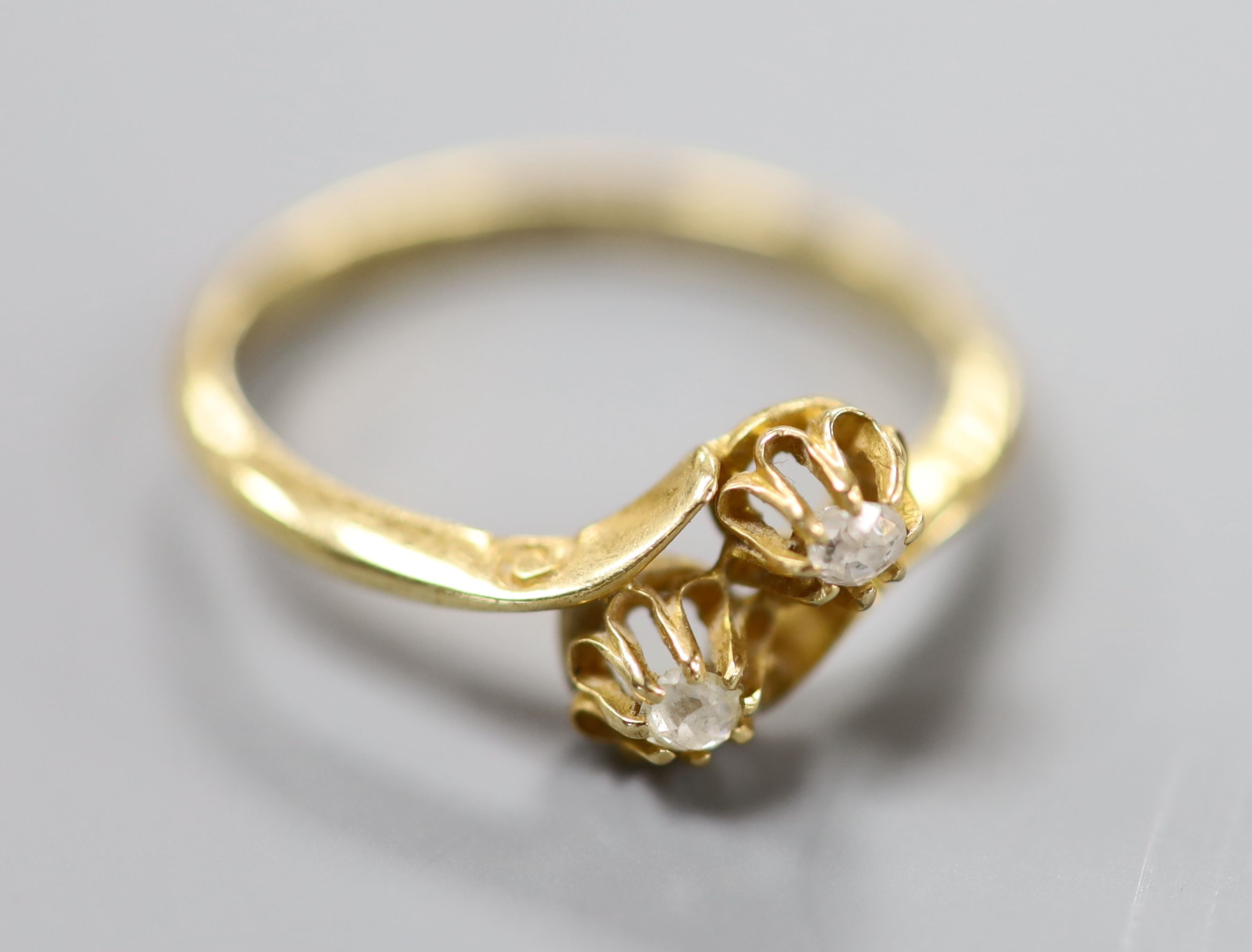 A George V 18ct gold and two stone diamond set crossover ring, size O/P, gross 2.7 grams.