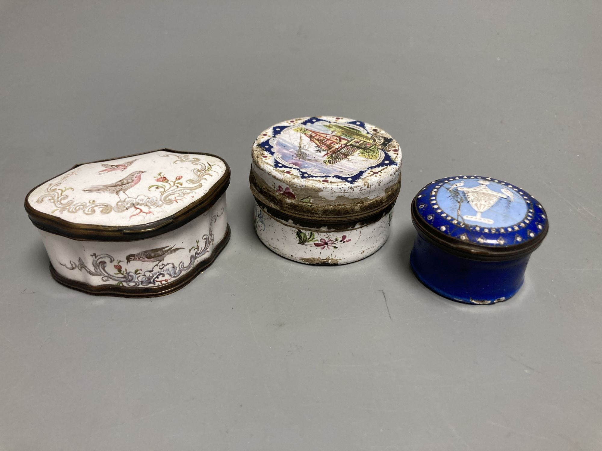An 18th century white enamelled box painted with a palace, 5cm., a cartouche shaped box decorated
