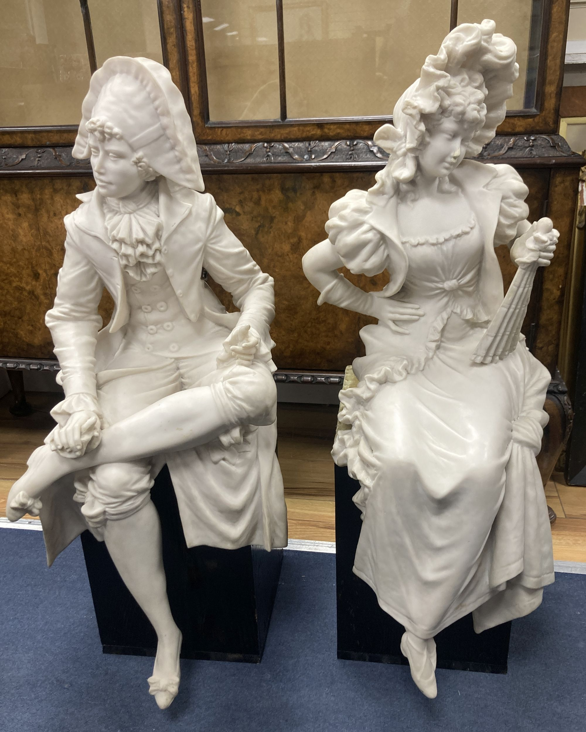 A pair of resin marble seated figures of a Dandy and a Dandizette on ebonised plinths