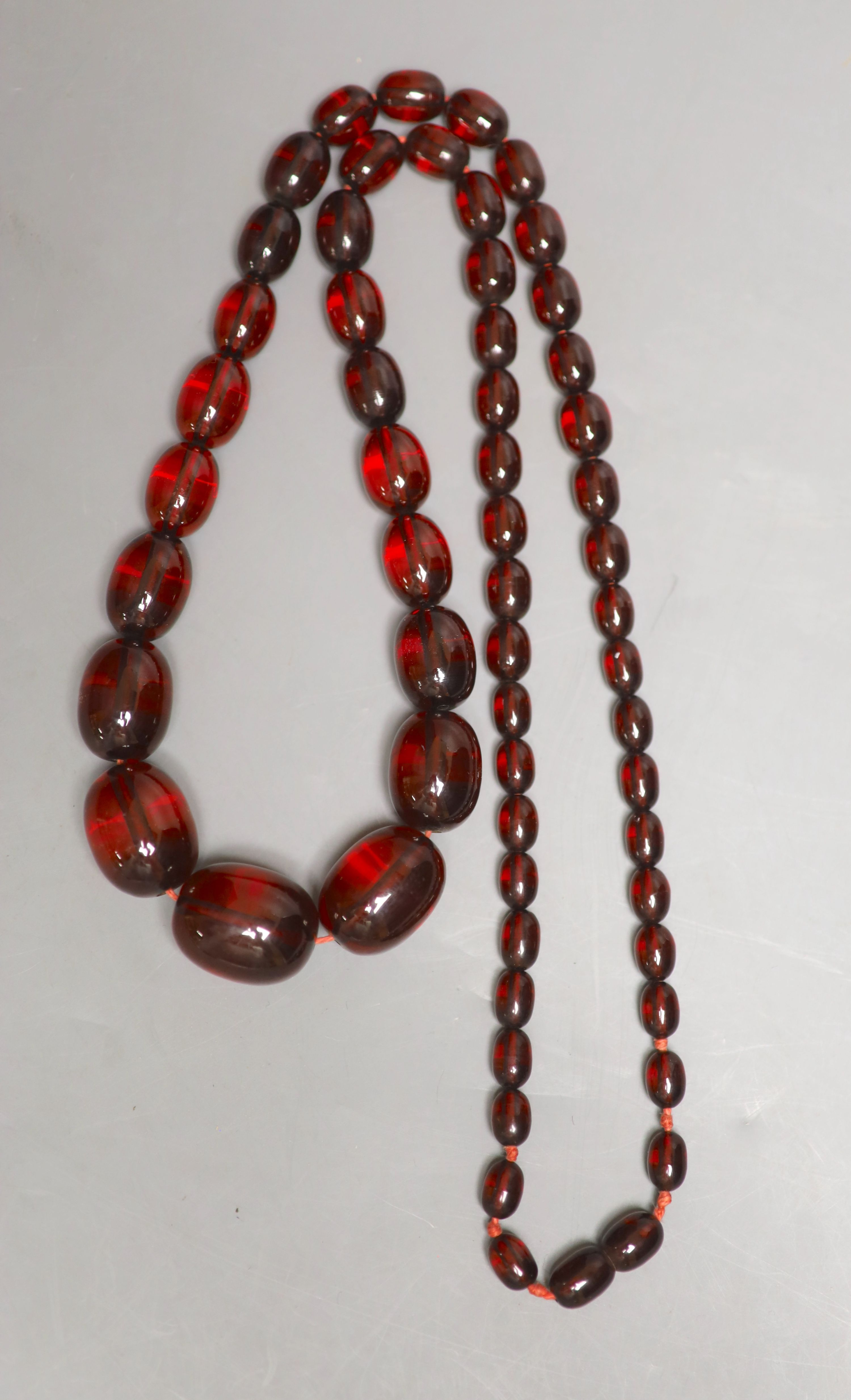 A single strand graduated oval simulated cherry amber bead necklace, 84cm, gross 90 grams. - Image 2 of 2
