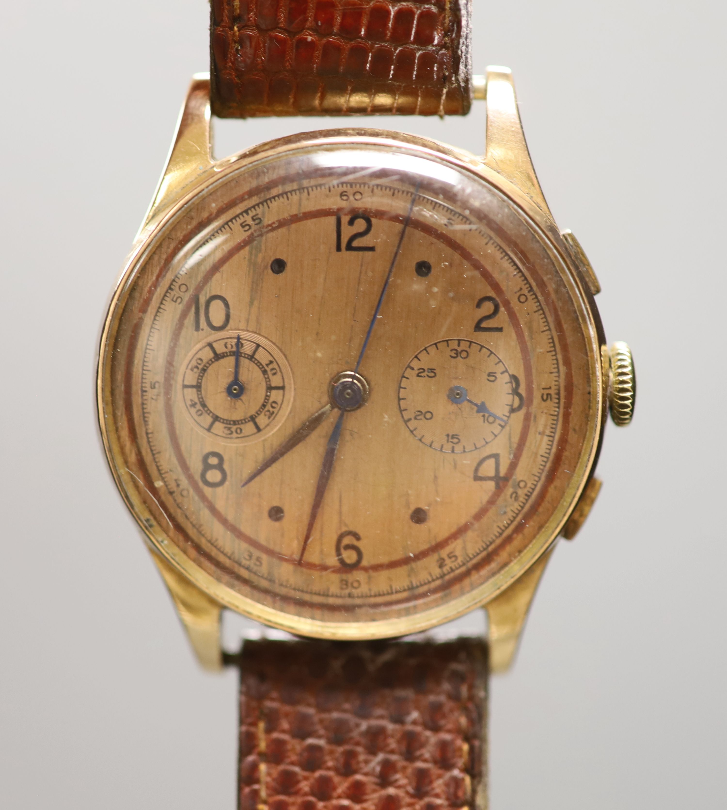 A Swiss 18k yellow metal chronograph manual wind wrist watch, on associated leather strap, with a