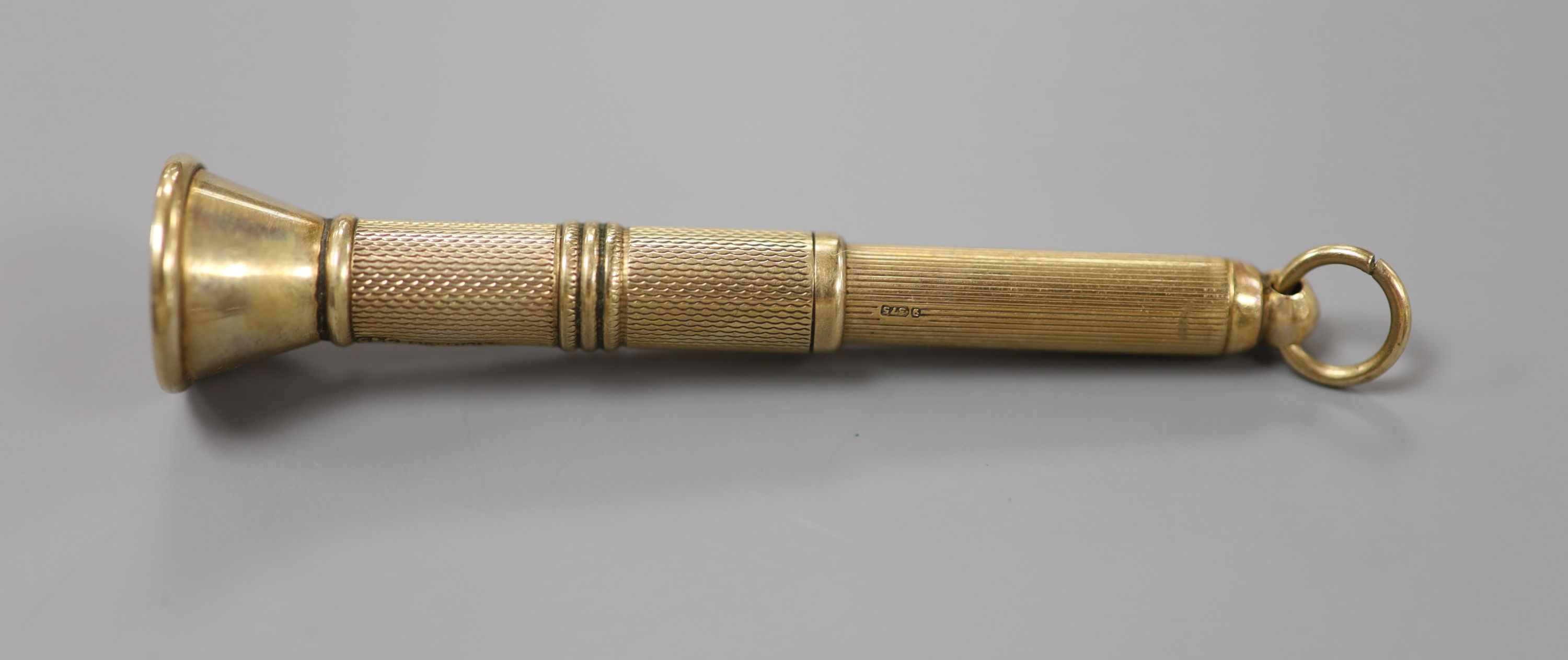 A mi 20th century engine turned 9ct gold cased cigar piercer, 67mm, gross 8.6 grams.