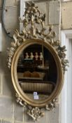 An oval giltwood wall mirror, width 59cm, height 103cm
