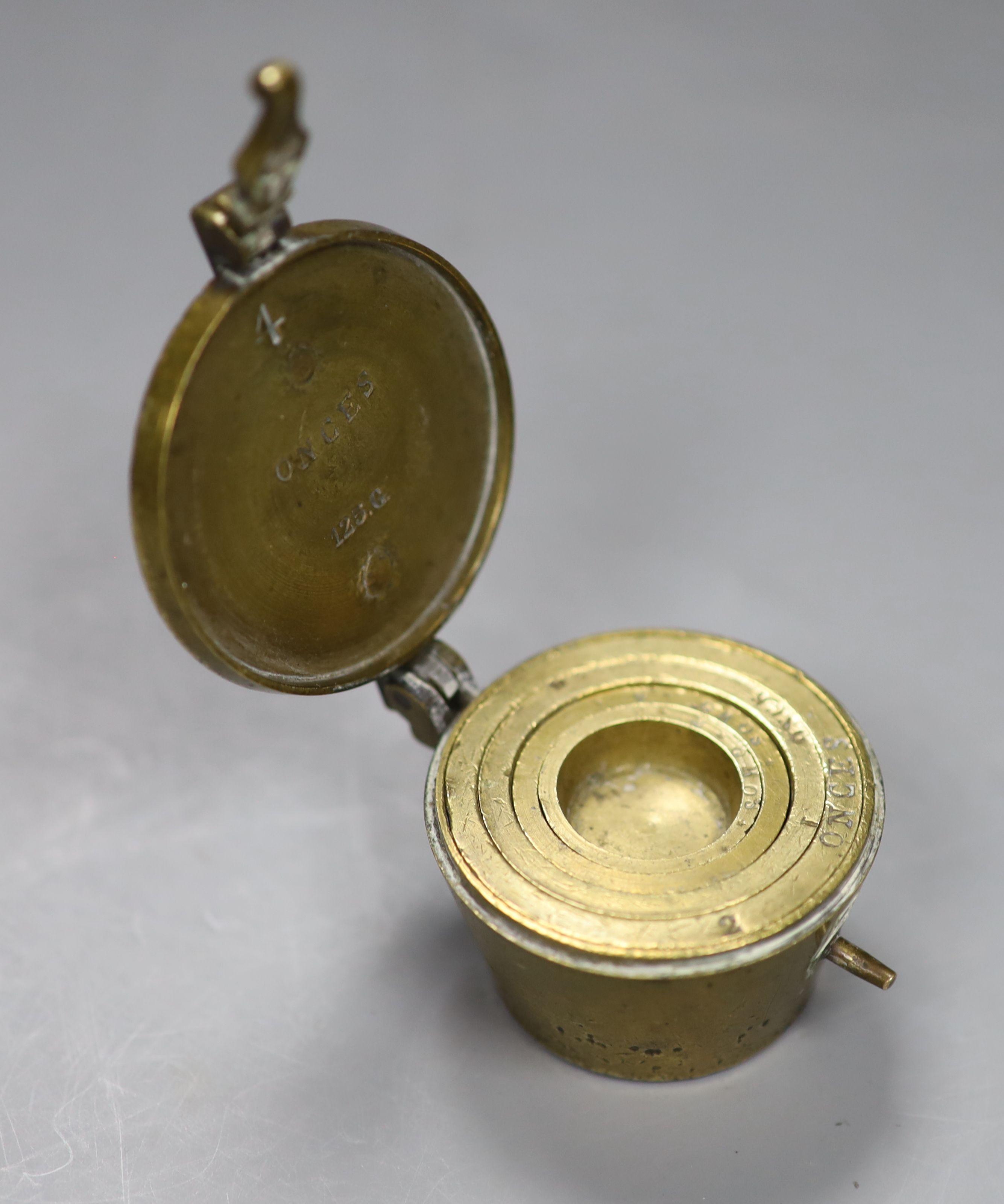 A Victorian brass 8 ounce cup weights
