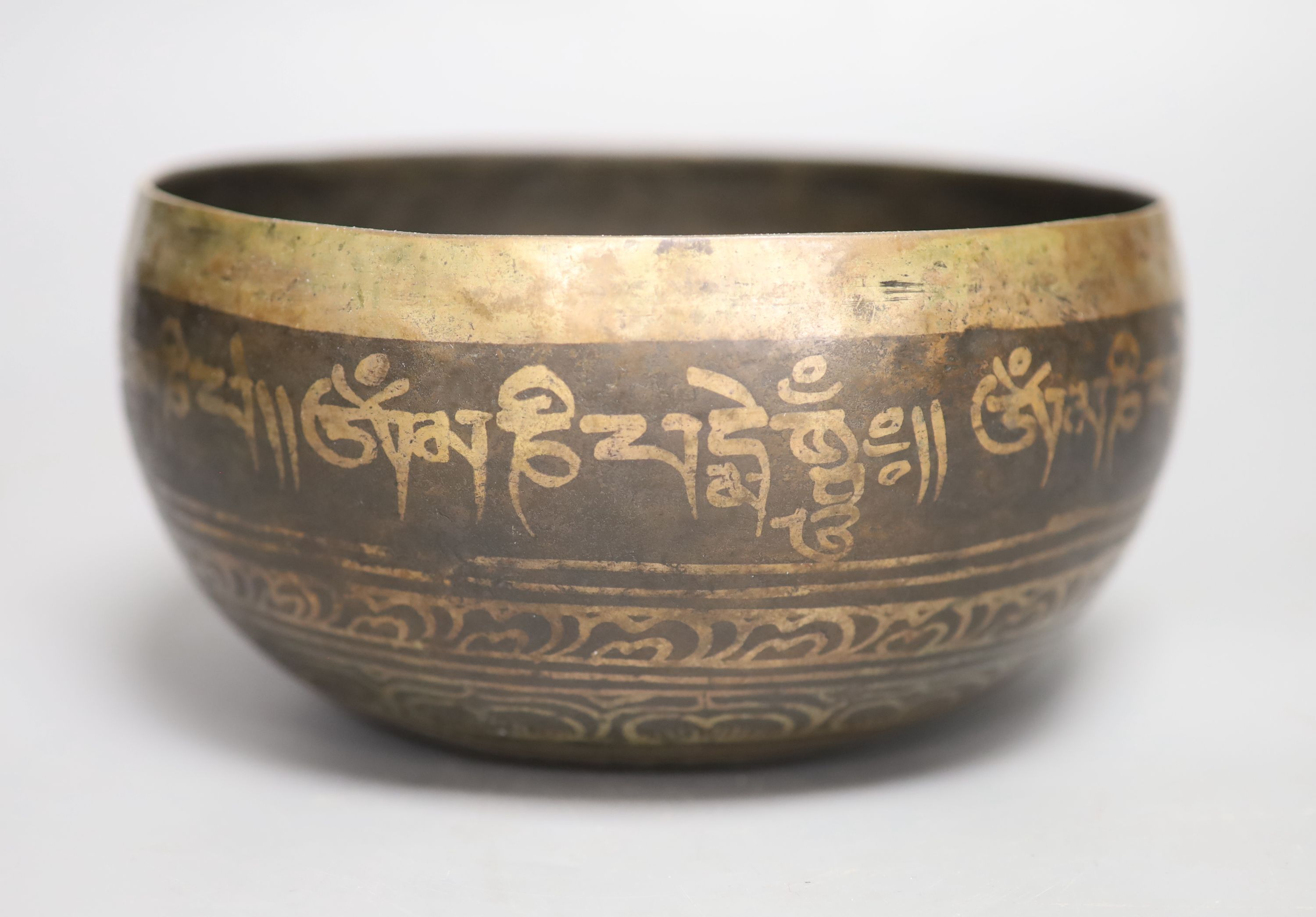 A Middle Eastern white metal and copper damascened bell, banded with foliate patterns and Arabic