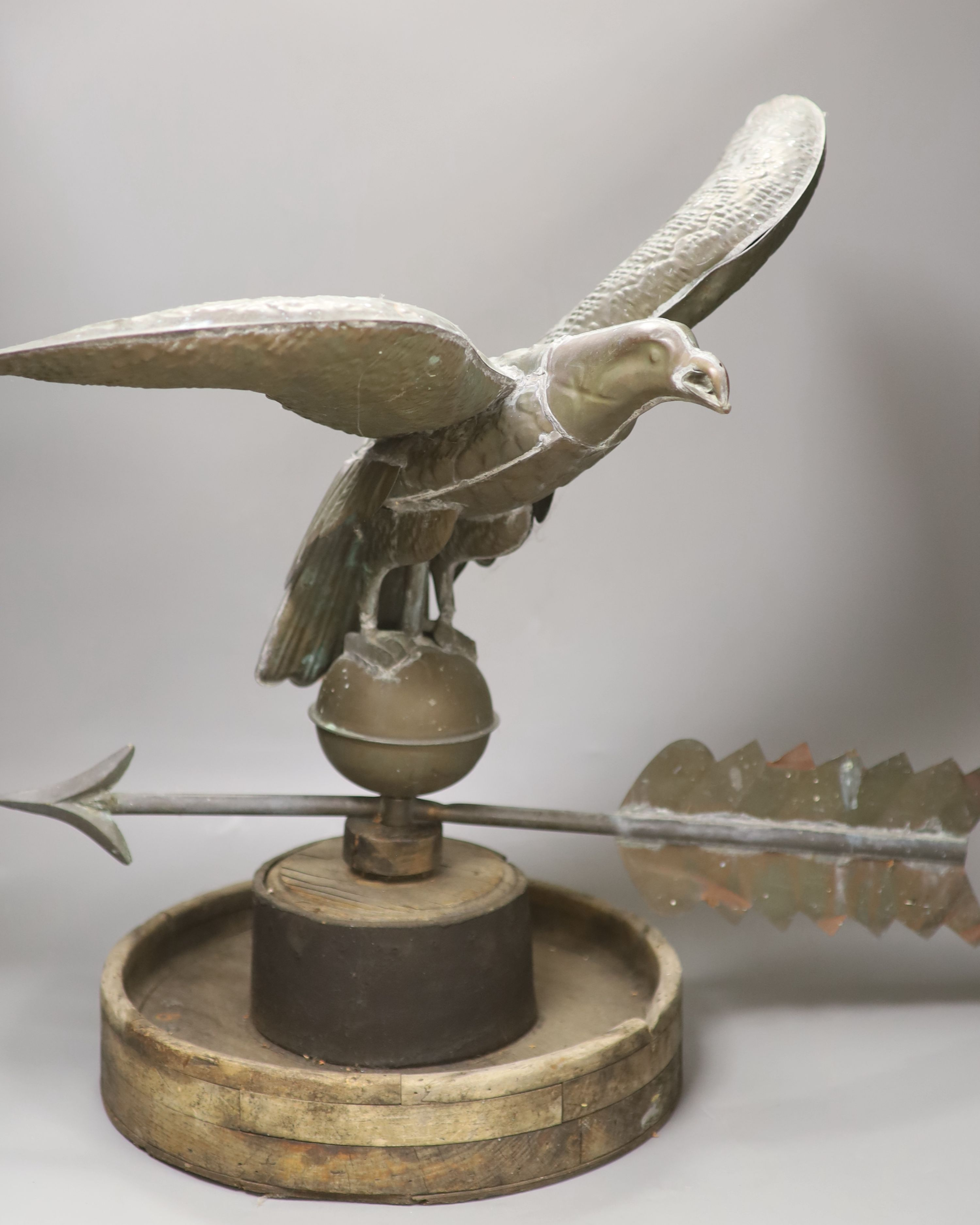 A 19th century American copper weather vane, modelled as an eagle, on an associated wooden base,